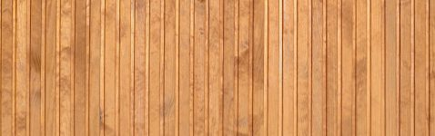 Close up of brown wooden fence panels. Many vertical wooden planks as a full wall